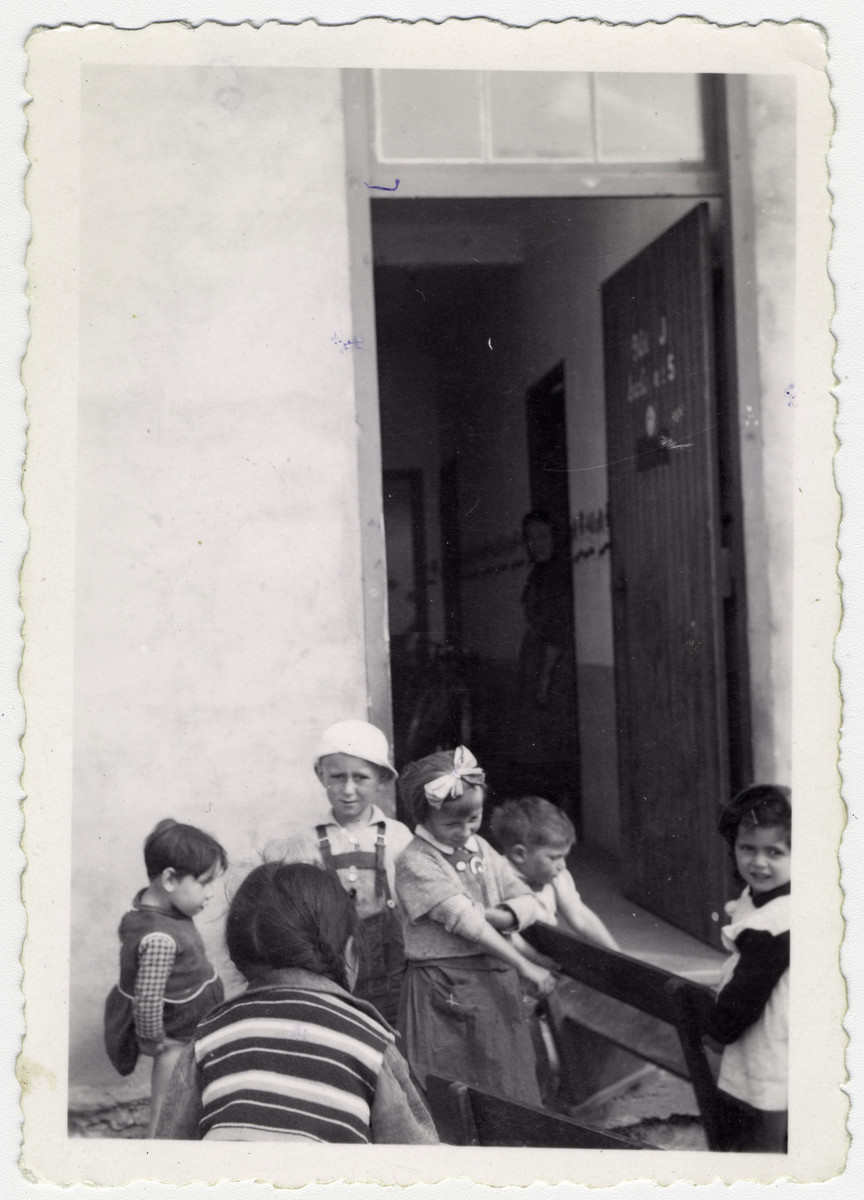 "A group of Jewish children stand outside of a building in Rivesaltes; two are carrying a bench.   Original caption reads: ""The Nursery School, Jewish children."""