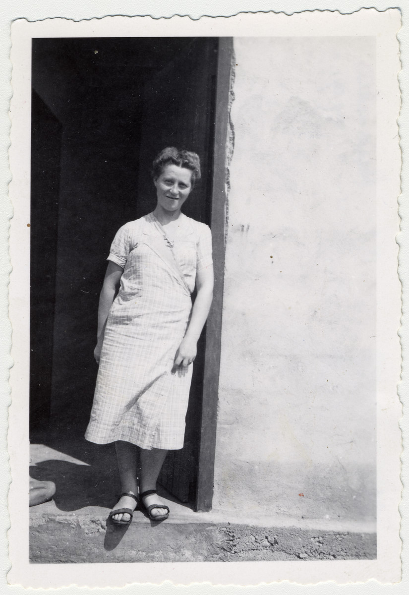 """A woman poses in the doorway of a barrack in the Rivesaltes internment camp.   The original caption reads: """"Madame Suessmann before her deportation, in front of our barrack."""""""