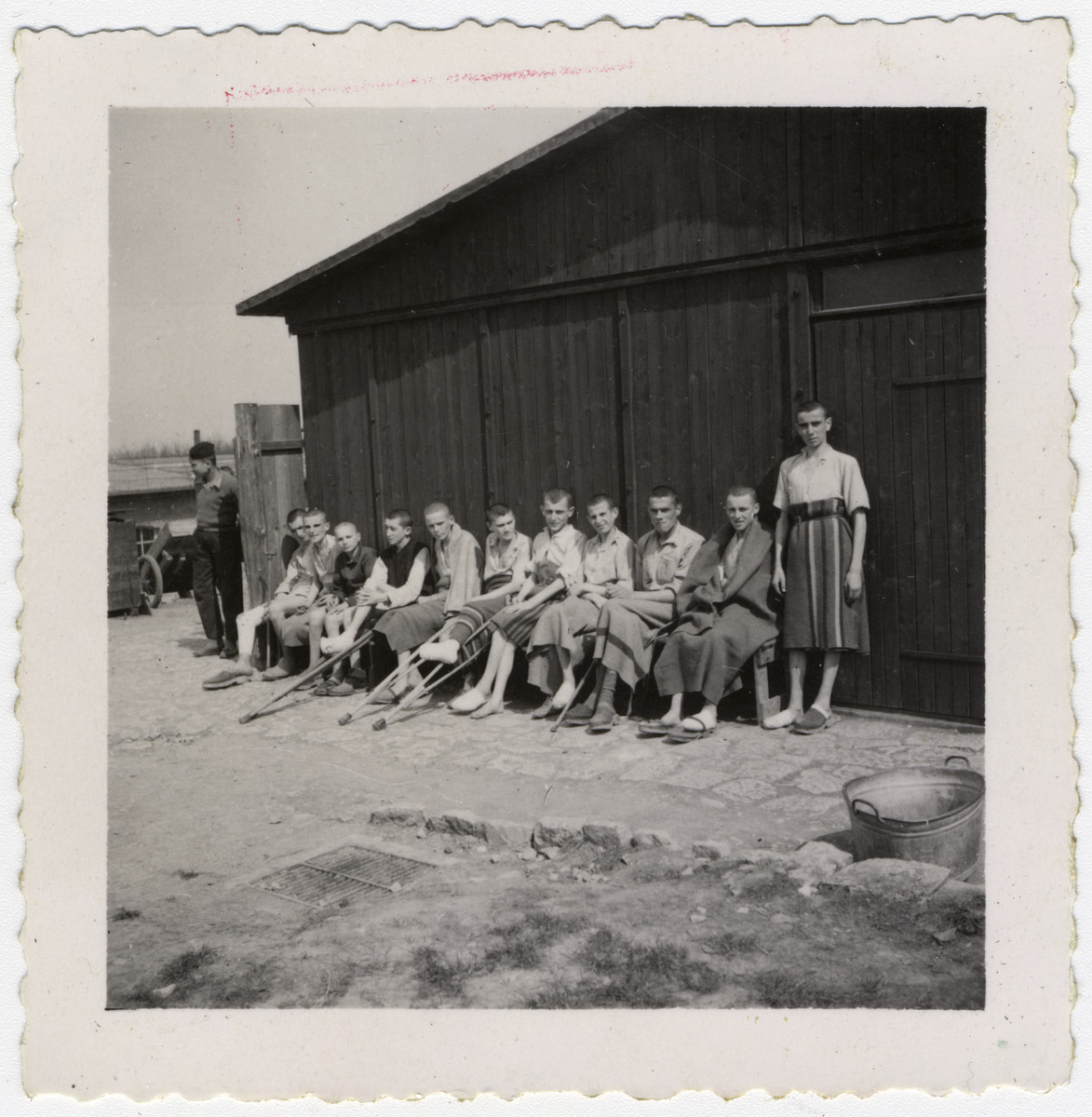 Survivors of the Buchenwald concentration camp, many with crutches, sit outside a barrack following liberation.