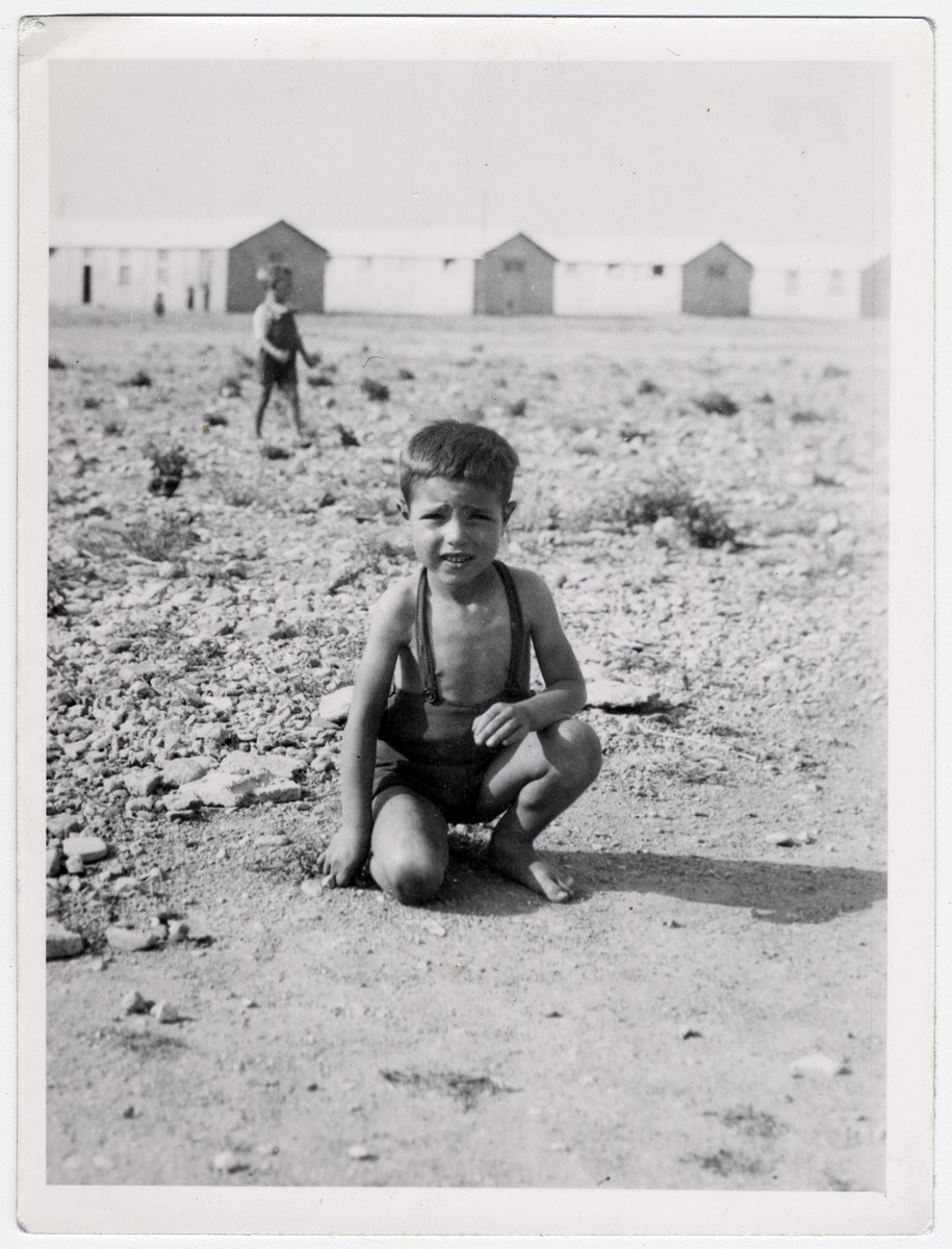 "A small boy [probably Spanish] crouches down, as he plays in the dirt in front of the barracks of the Rivesaltes internment camp.   Original caption reads: ""Pepito."""