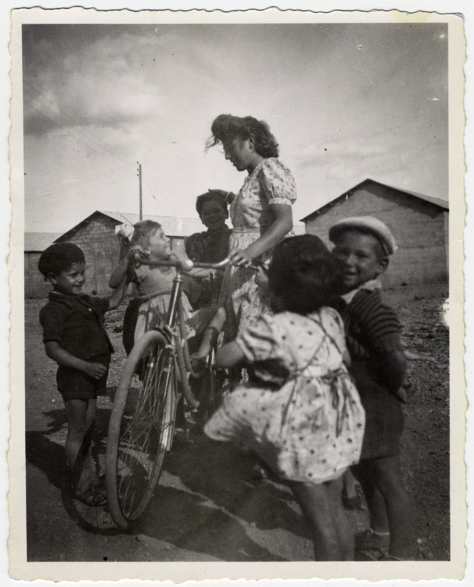 A group of children gathers around a Jacqueline Levy standing  with a bicycle at the Rivesaltes internment camp.