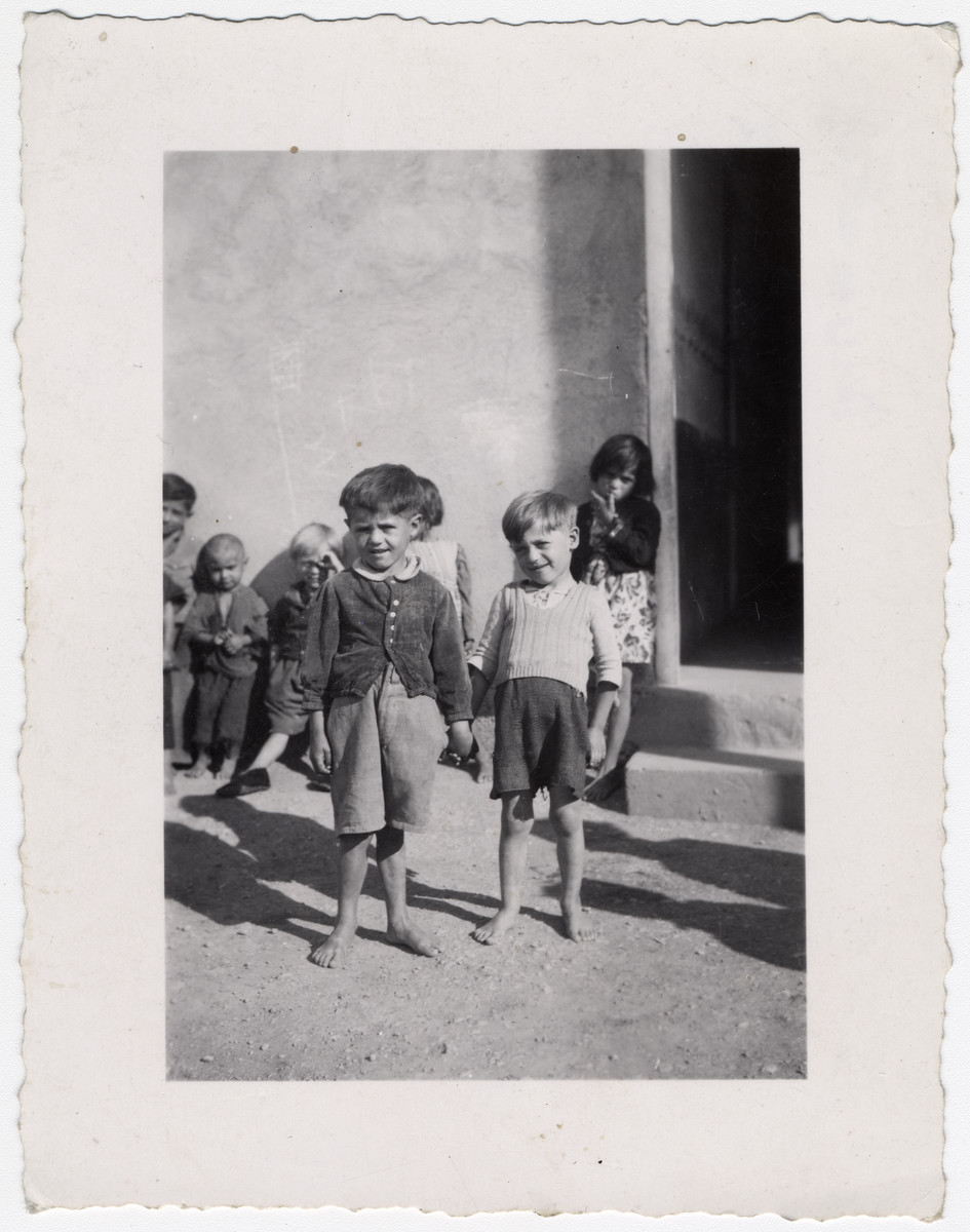 "Several young Roma children wait outside of a building, presumably for school in the Rivesaltes internment camp.   Original caption reads: ""Gypsies."""