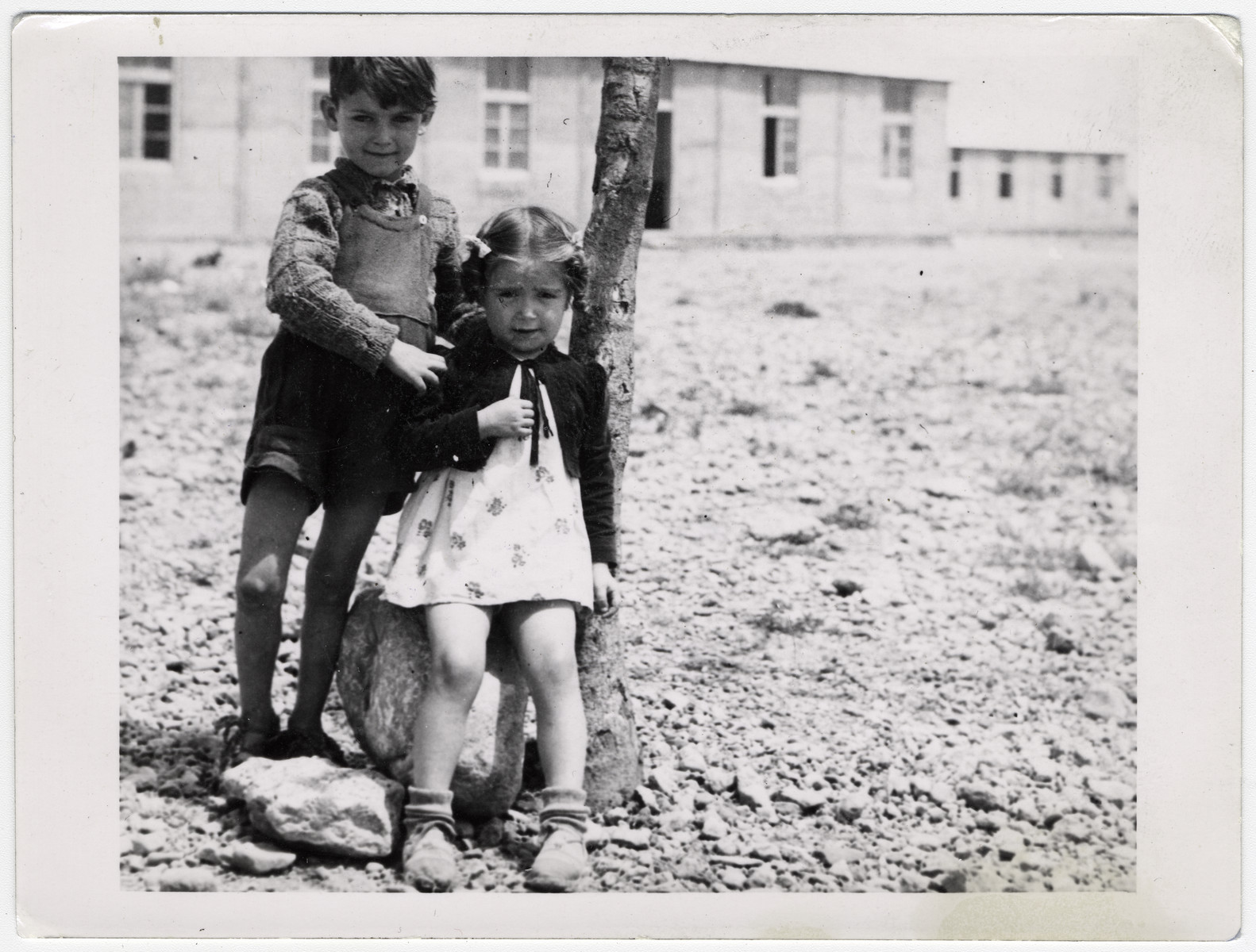 "A Spanish boy and girl stand outside next to a tree, in front of a school building at Rivesaltes.   Original caption reads: ""Two Spaniards of the nursery school."""