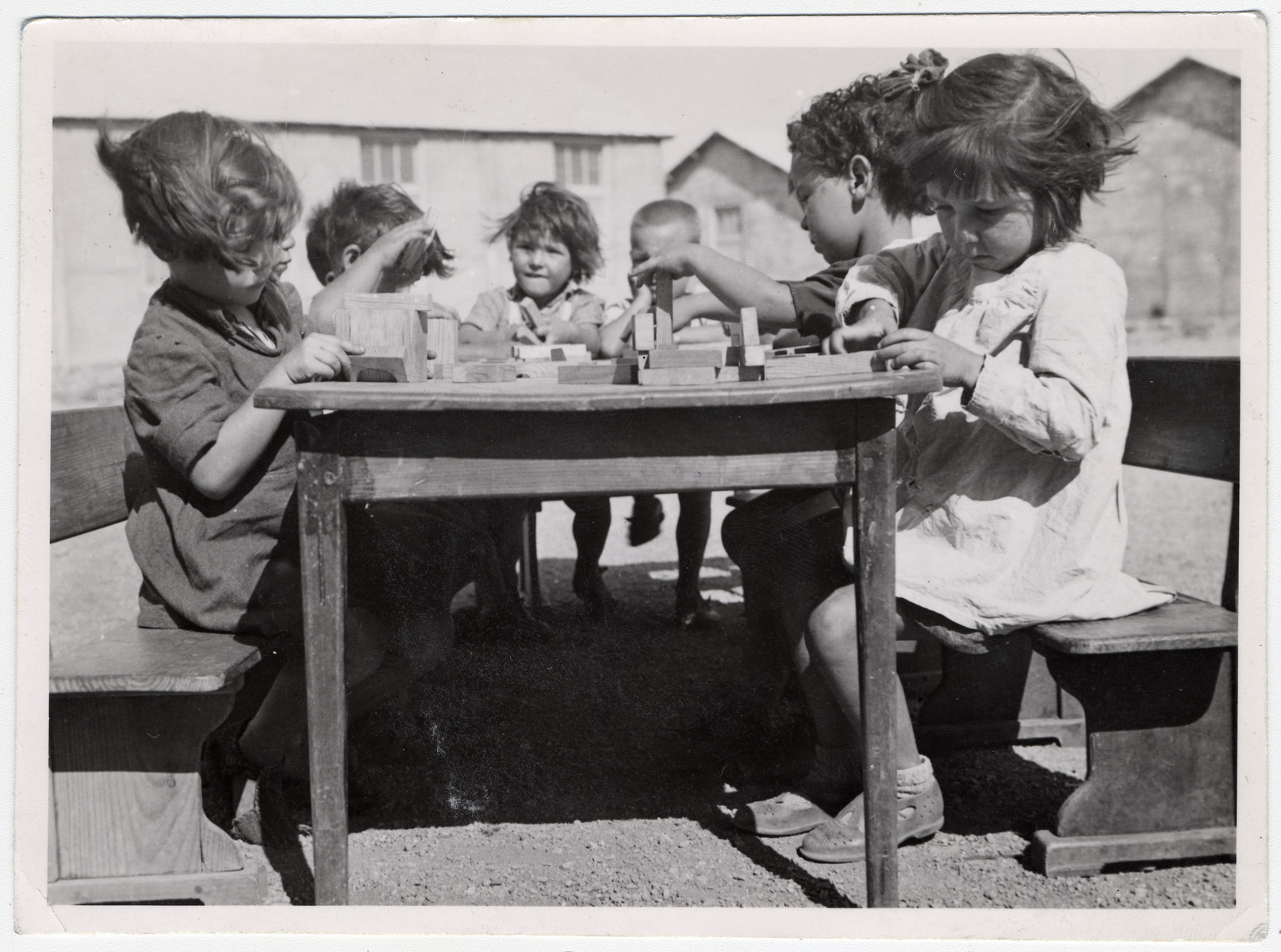 """A small group of Spanish children sit at a table in the Rivesaltes internment camp, playing with blocks.   Original caption reads: """"A group of Spaniards."""""""