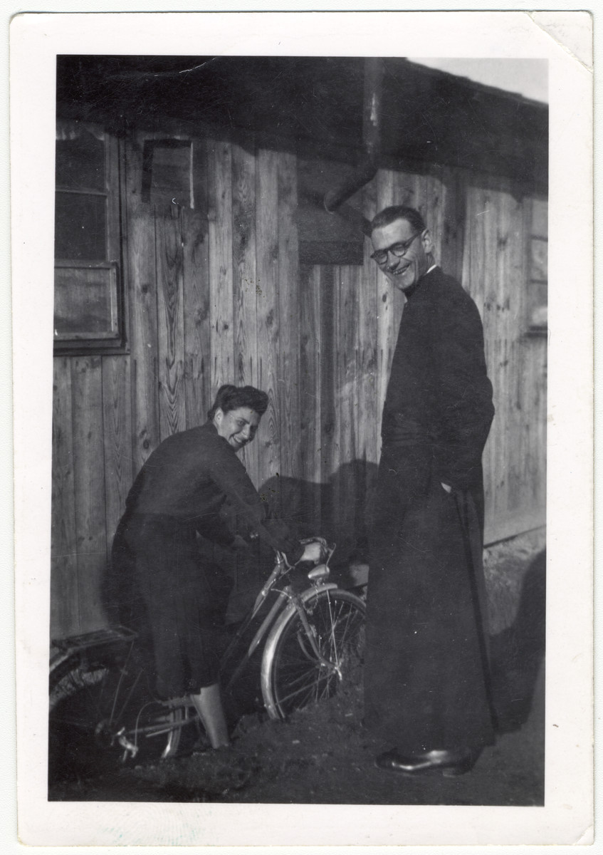 Madeleine Barot riding a bicyle and a Christian clergyman [probably Father Dumas] pose outside of a building in the Gurs internment camp.