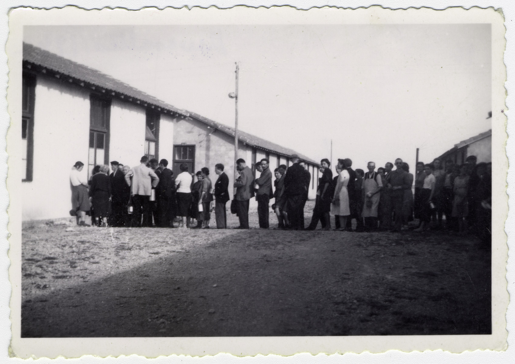 """A line of prisoners wait to be served their rations at the Rivesaltes internment camp.   Original caption reads: """"The line for soup."""""""