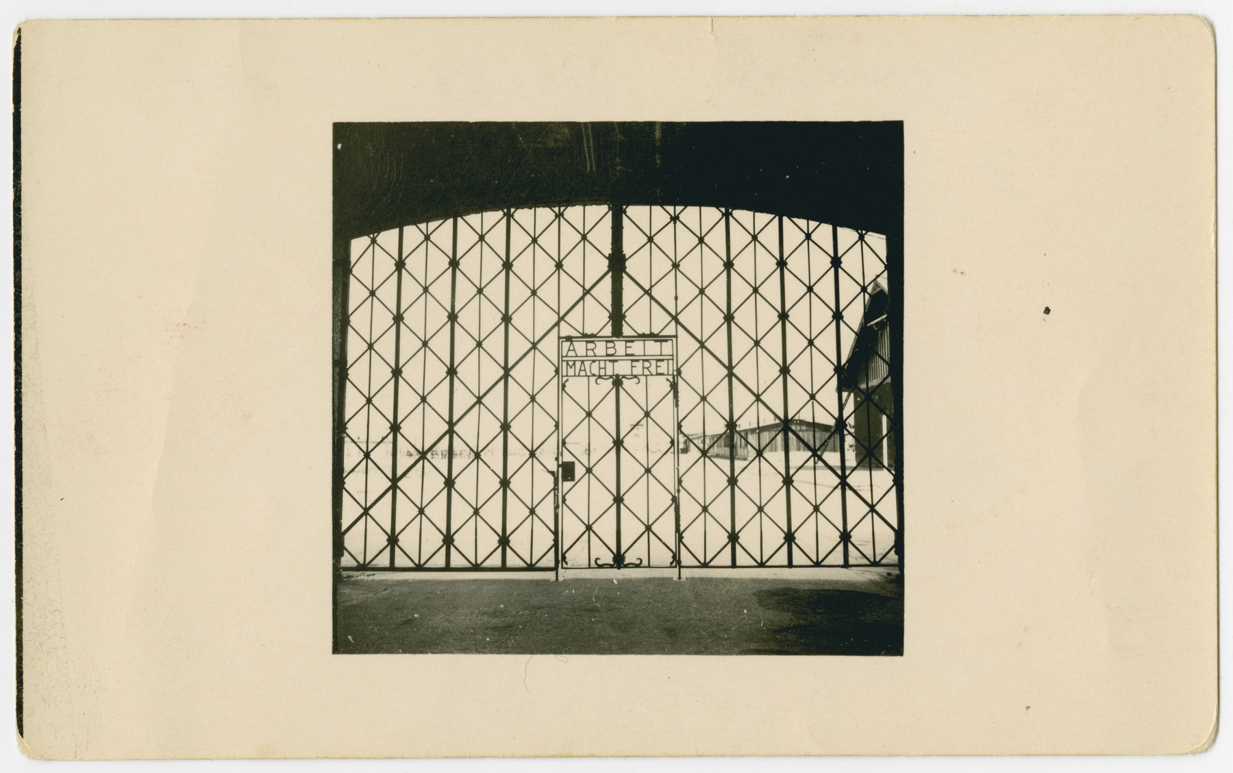 "View of the gated entrance to the Dachau concentration camp with the sign, ""Arbeit Macht Frei"" [Work makes you free]."