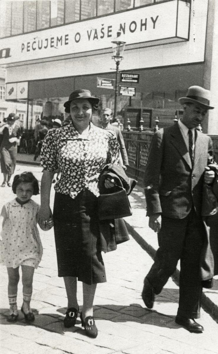 The Eckstein family walks down a street of prewar Bratislava.  Pictured from left to right are Eva, Helena and Eugene Eckstein.