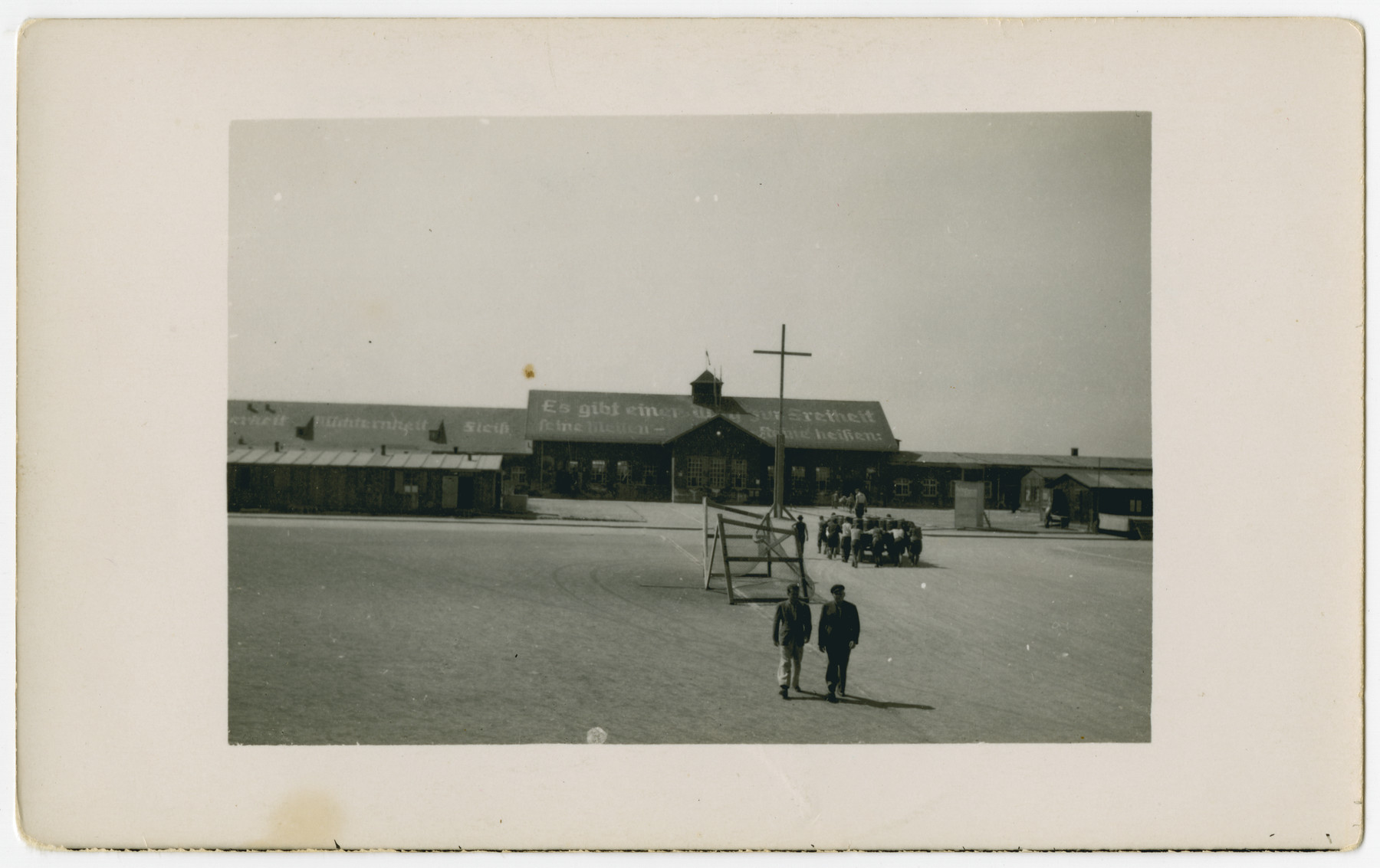 "Two survivors walk through the central courtyard of the Dachau concentration camp while a larger group pushes a wagon in the background.  The original caption reads: ""Cart for hauling dead prisoners."""