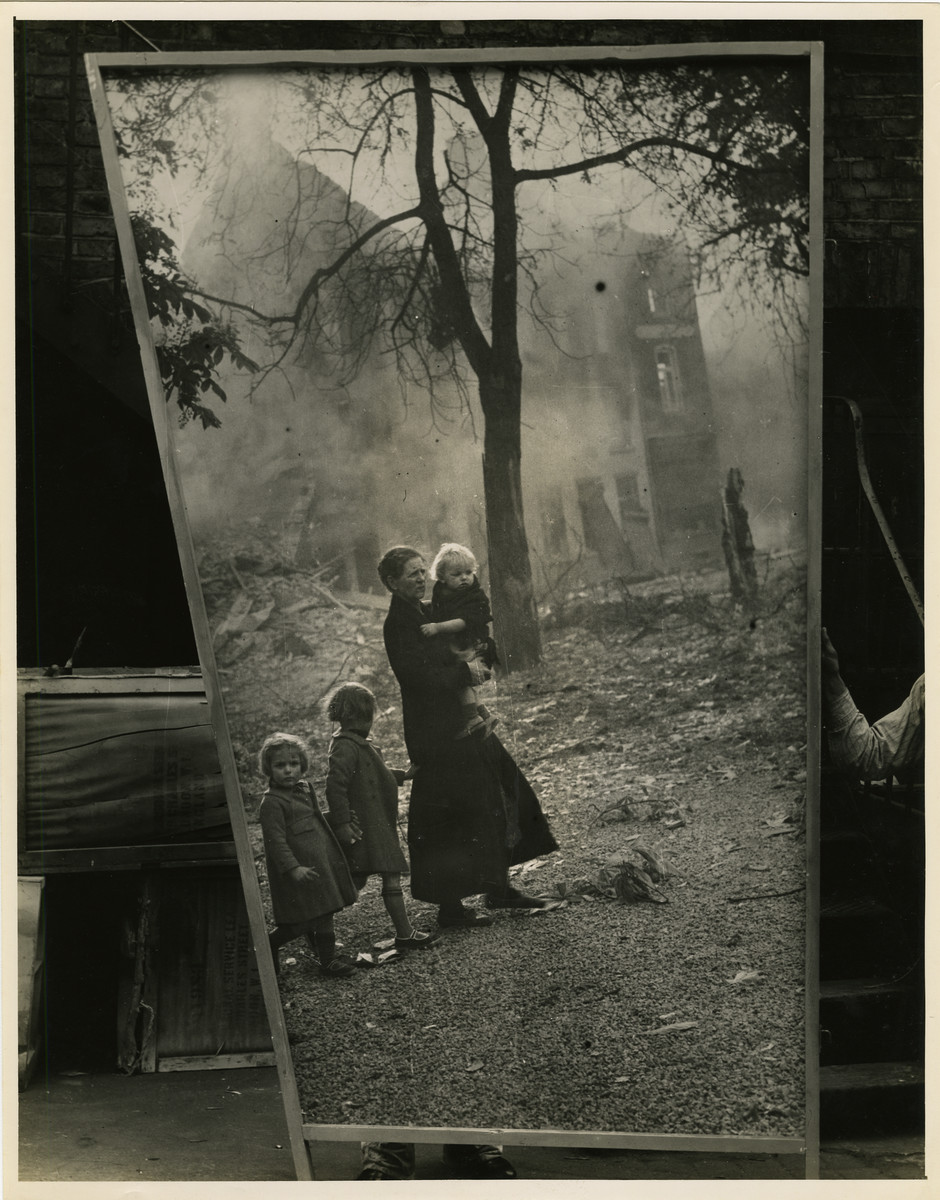 "Panel from a 1944 exhibition in London, England entitled ""Germany- the Evidence"" showing a woman and young children near a destroyed building.   The back of the photo reads ""British Official Photograph; Distrbuted by the Ministry of Information. D. ; The Evil We Fight.; Ministry of Information Exhibition priduced by Display & Exhibitions Division for show all over Great Britain.; Display panel"""