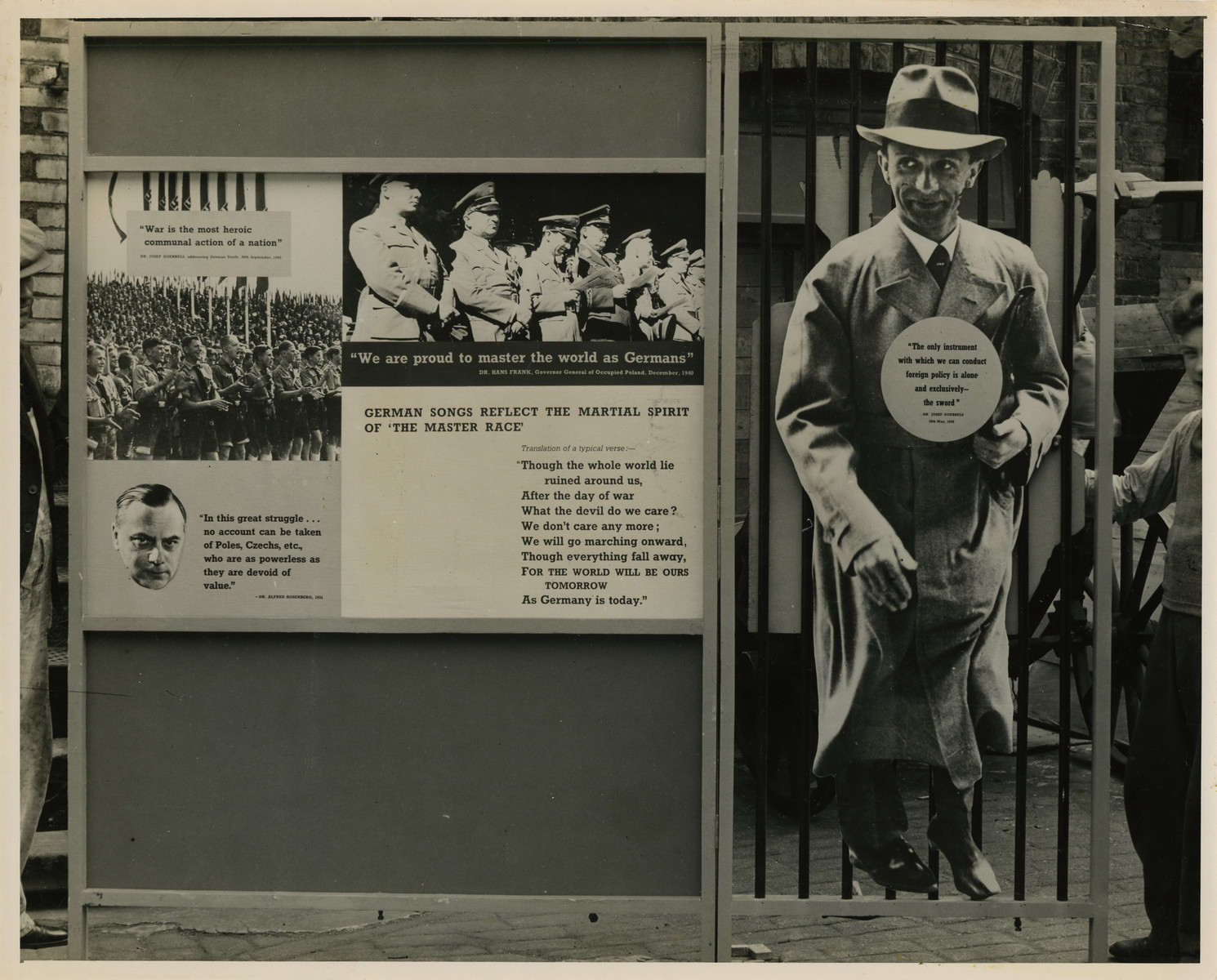 "Panel from a 1944 exhibition in London, England, entitled ""Germany- the Evidence"" showing Joseph Goebbels.   The left panel shows anti-Nazi and anti-German sentiment stating the Nazis' desire to master the world. The left panel shows Dr. Joseph Goebbels with a quotation: ""The only instrument with which we can conduct foreign policy is alone and exclusively- the sword.""  The back of the photo reads ""British Official Photograph; Distrbuted by the Ministry of Information. D. ; The Evil We Fight.; Ministry of Information Exhibition priduced by Display &Exhibitions Division for show all over Great Britain.; Display panel"""