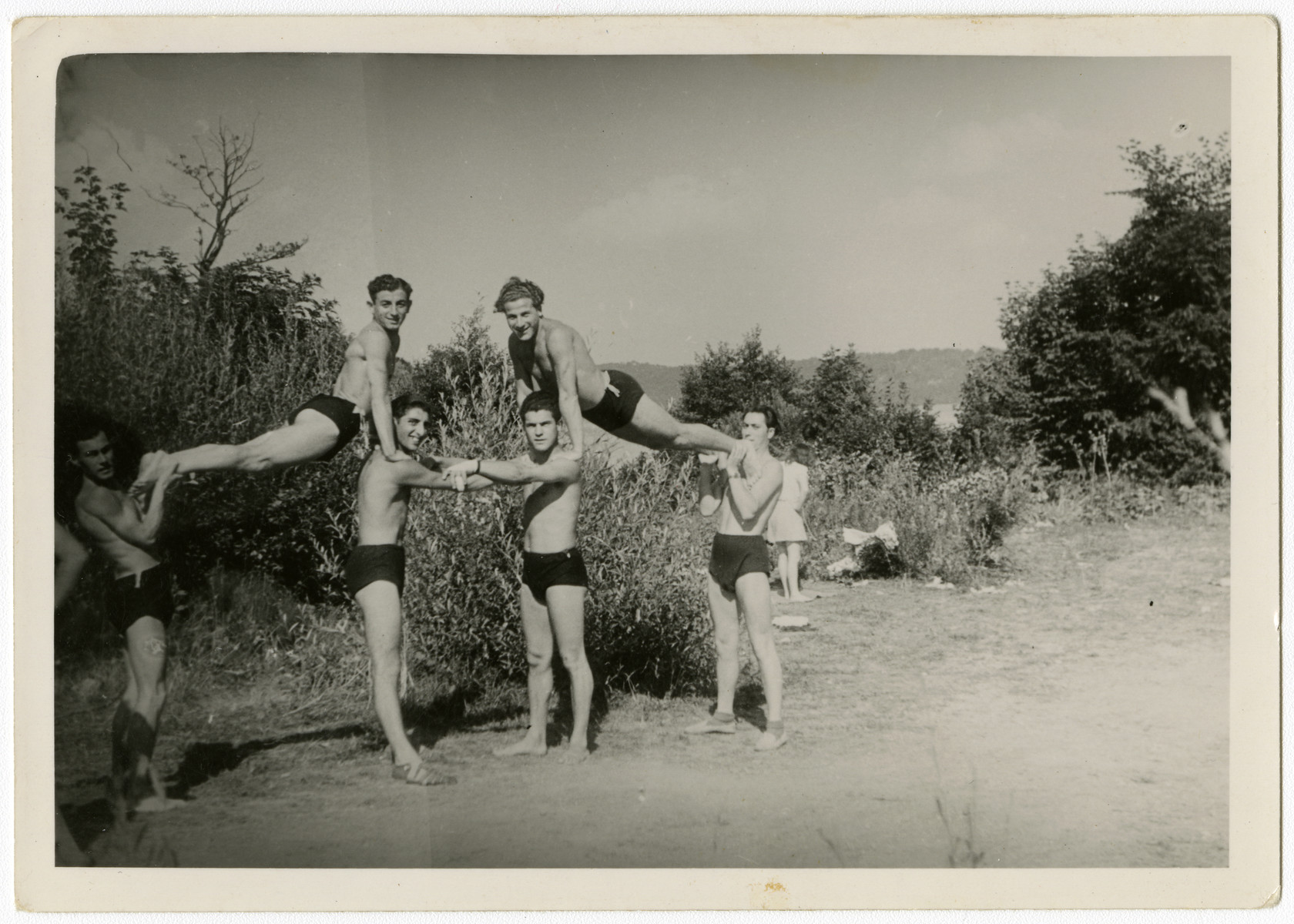 Young men in the Feldafing displaced persons camp do gymnastics.  Chamek (Harry Weinroth) is pictured second from the left on the bottom.  On the top right is Jaszke Aronowitz (Jack Arnel).