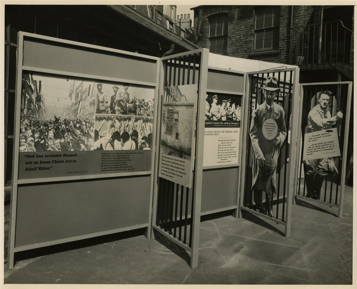"Panel from a 1944 exhibition in London, England, entitled ""Germany- the Evidence"" showing Nazi military sentiment.   The panel shows Joseph Goebbels and Adolf Hitler as well as numerous military shots of the Nazi Regime. Next to the pictures are quotations from Nazi personnel.  The back of the photo reads ""British Official Photograph; Distrbuted by the Ministry of Information. D. ; The Evil We Fight.; Ministry of Information Exhibition priduced by Display &Exhibitions Division for show all over Great Britain.; Display panel"""