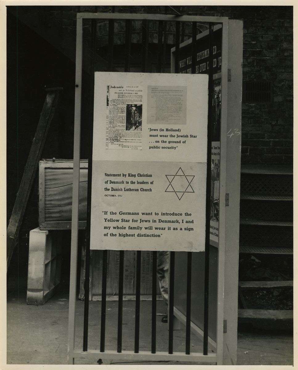 """Panel from a 1944 exhibition in London, England, entitled """"Germany- the Evidence"""" showing resistance to the Nazi Regime in Holland and Denmark.   A panel that reads """"Jews (in Holland) must wear the Jewish Star... on the ground of public security."""" """"Statement by King Christian of Denmark to the leaders of the Danish Lutheran Church. October 1943. If the Germans want to introduce the Yellow Star for Jews in Denmark, I and my whole family will wear it as a sign of the highest distinction.""""   The back of the photo reads """"British Official Photograph; Distrbuted by the Ministry of Information. D. ; The Evil We Fight.; Ministry of Information Exhibition priduced by Display &Exhibitions Division for show all over Great Britain.; Display panel"""""""