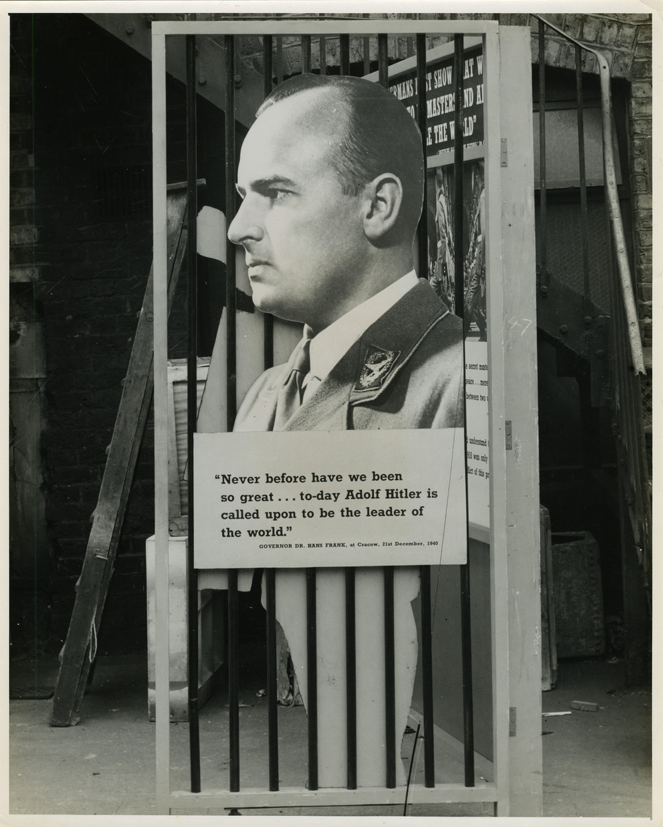 """Panel from a 1944 exhibition in London, England, entitled """"Germany- the Evidence' showing Hans Frank.   The panel shows a quotation from Hans Frank:""""'Never before have we been so great... to-day Adolf Hitler is called upon to be the leader of the World.' Governor Hans Frank 21st December 1943""""  The back of the photo reads """"British Official Photograph; Distrbuted by the Ministry of Information. D. ; The Evil We Fight.; Ministry of Information Exhibition priduced by Display &Exhibitions Division for show all over Great Britain.; Display panel"""""""
