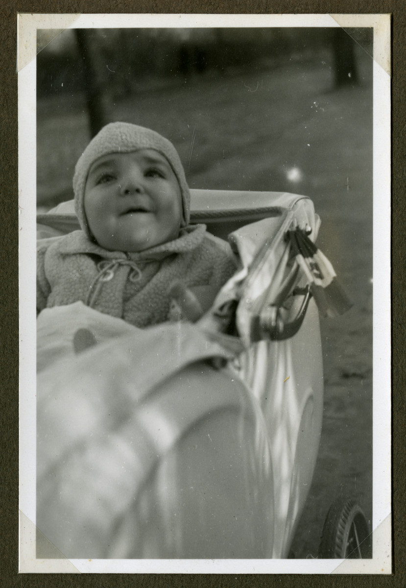 Romano Pelligrino sits in his baby carriage.    Attached to the carriage is an Italian flag.  Helga Pelligrino became an Italian citizen and was able to move about unmolested as long as she displayed the Italian flag on the baby carriage.