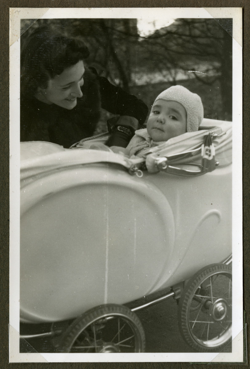 Helga admiries her baby son Romano who sits in his carriage.    Attached to the carriage is an Italian flag.  Helga became an Italian citizen and was able to move about unmolested as long as she displayed the Italian flag on the baby carriage.