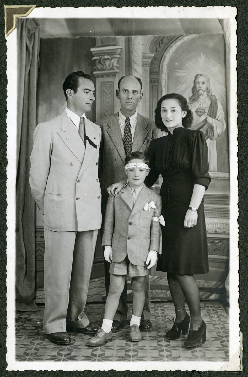Romano Pelligrino poses with his parents, Helga and Mario and an unidentified man in front of a painting of Jesus.  Romano is wearing a white armband and his father is wearing a black mourning badge.