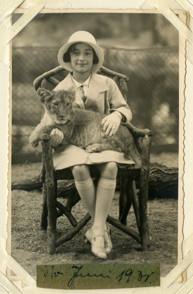Helga Reinsch sits with a baby lion in her lap.