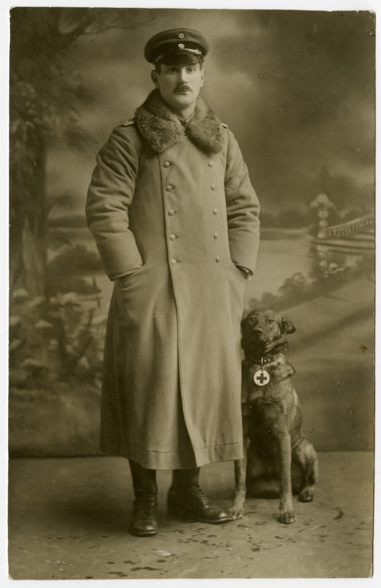 A portrait of Karl Reinsch in military uniform with a service dog bearing a Red Cross tag.