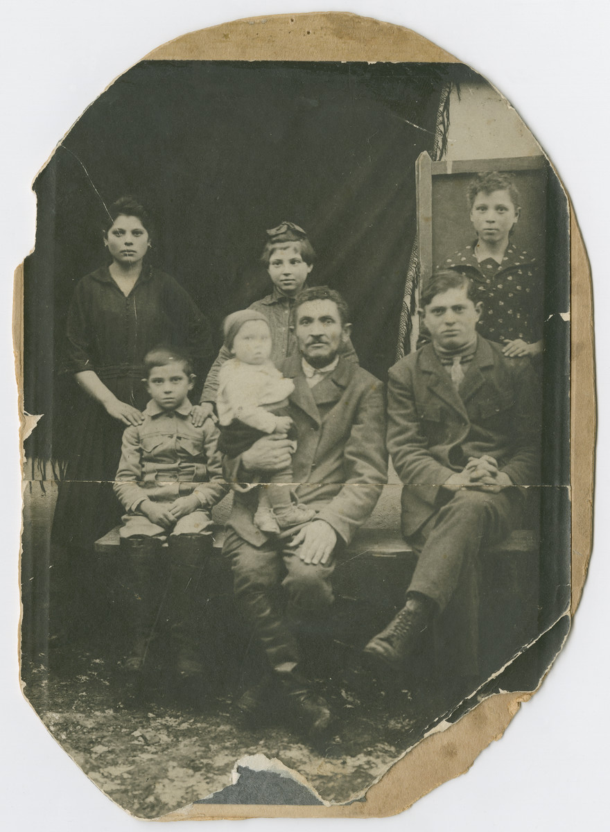 Portrait of the Braziler family.    Pictured  are Brane, Libe, and Sylvia Braziler. Copl Braziler is seated at center holding his infant son George (later Bresalier).  Two unidentified family members are also present  George and Sylvia Braziler were the only members of their immediae family to survive the Holocaust.