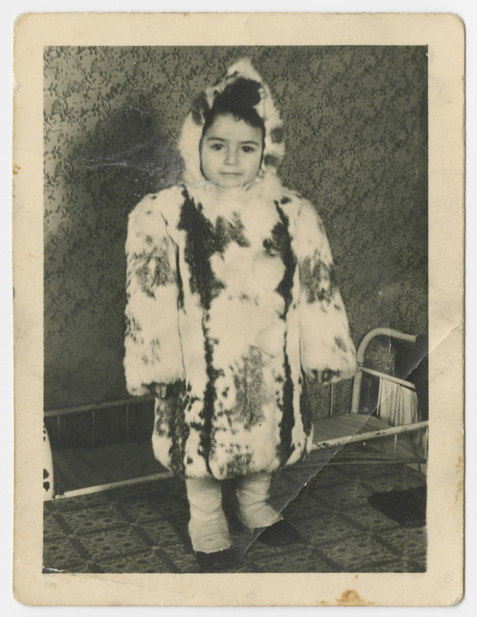 Ellen Zinger stands either in the Bergen-Belsen displaced persons camp while wearing a fur coat and hat.
