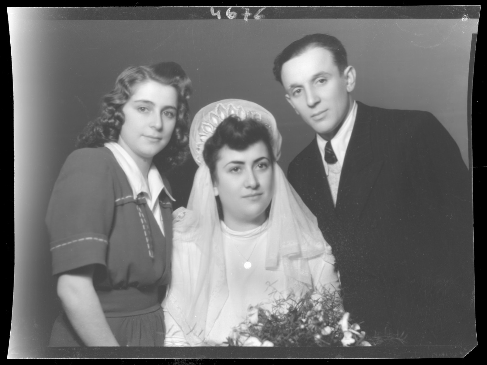 Studio wedding portrait of Miklos Grun, his bride and another woman.
