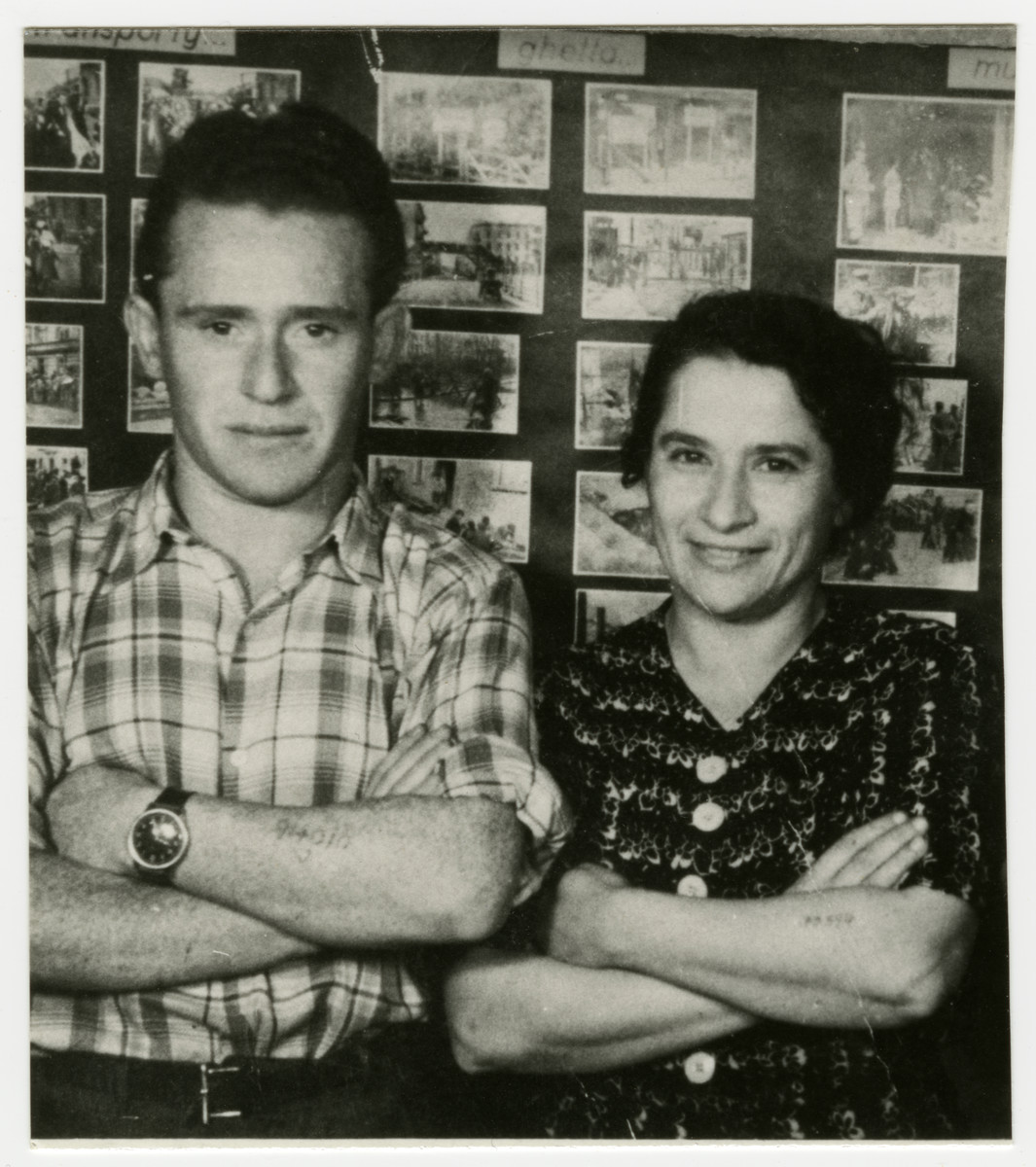 Bronislaw Gelczynski (Abraham Gordon) and an unidentified woman pose in front of a display of Holocaust photographs.
