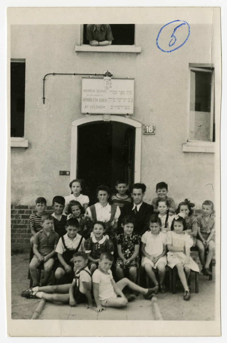 Solomon Manishewitz, the founder and principal of the Henreitta Szold Hebrew school, sits next to a teacher in front of the school.  They are surrounded by fouth grade students.
