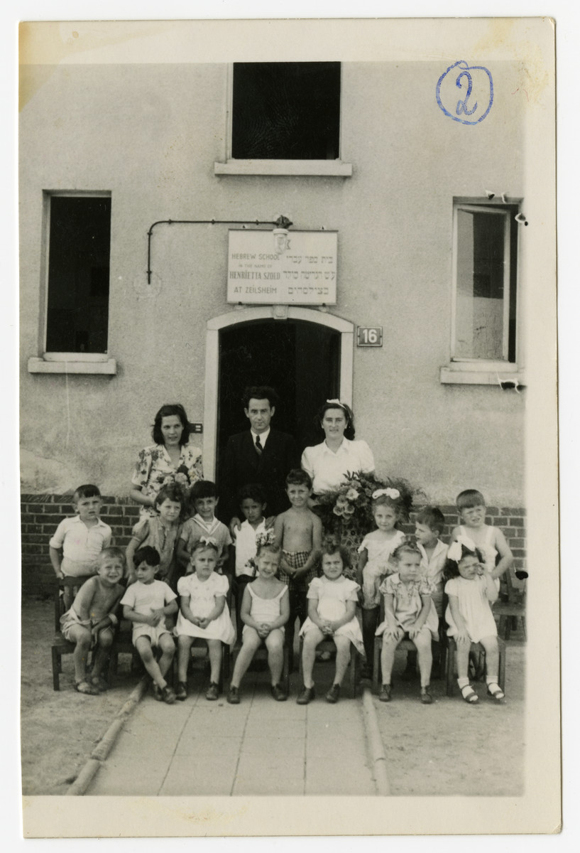 The founder and principal of the Henrietta Szold Hebrew School, Solomon Manischewitz, and two teachers stand behind the first grade students at the enrance of the school at the Zeilsheim DP center.