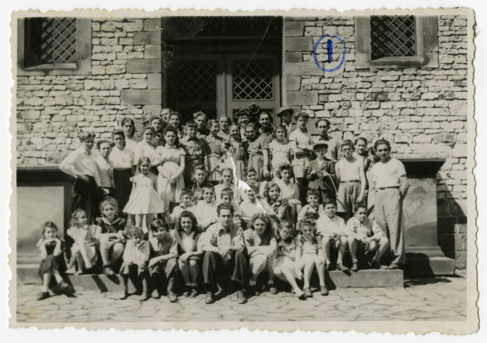 Group portrait of students and teachers of the Henrietta Szold Hebrew school in the Zeilsheim DP center.  Solomon Manischewitz, the founder and principal of the school, is seated in the middle of the front row.