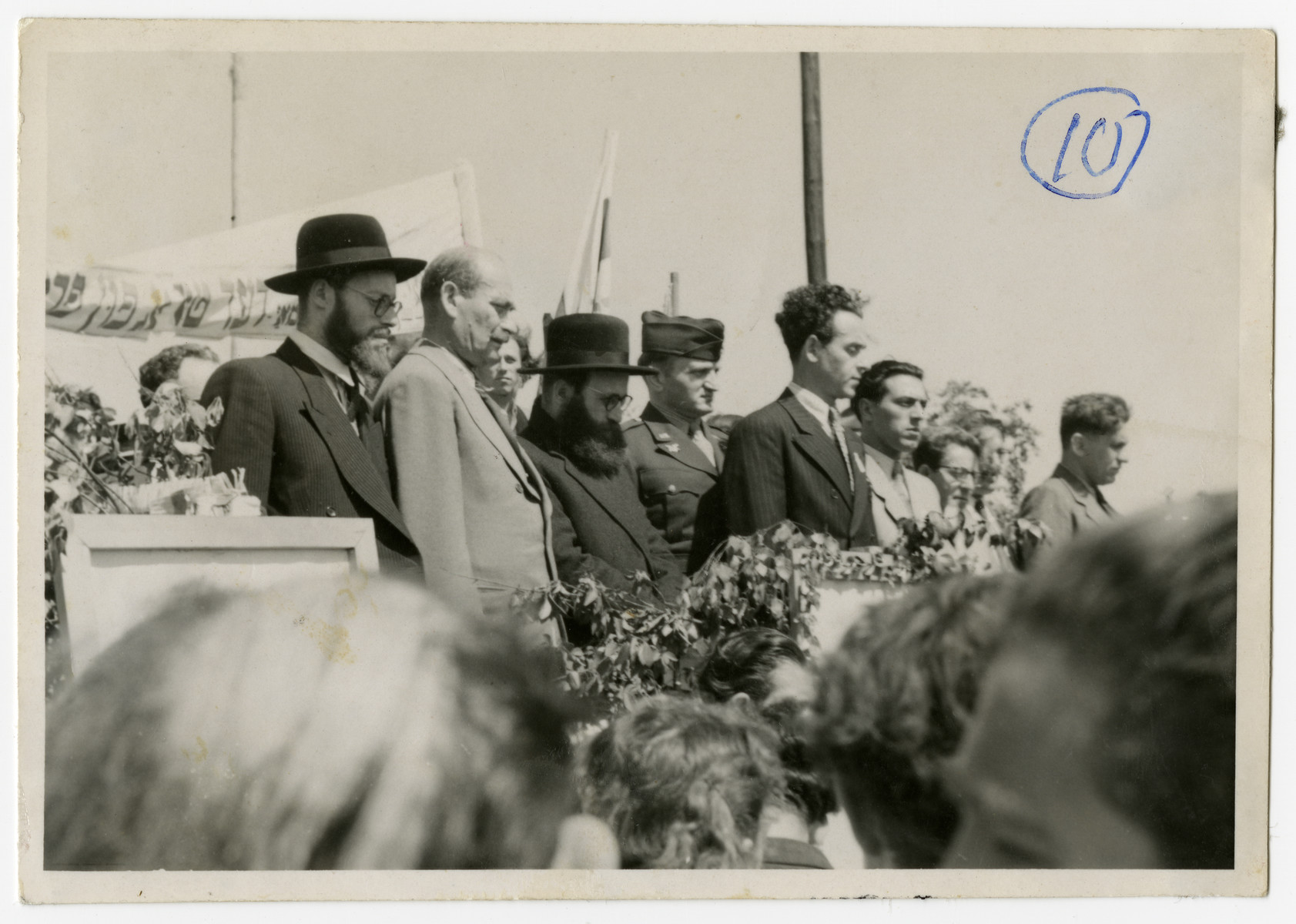 Solomon Manischewitz, standing center in a striped suit, leads a crowd assembled in singing the Hatikva on the day of the Proclamation of the State of Israel.