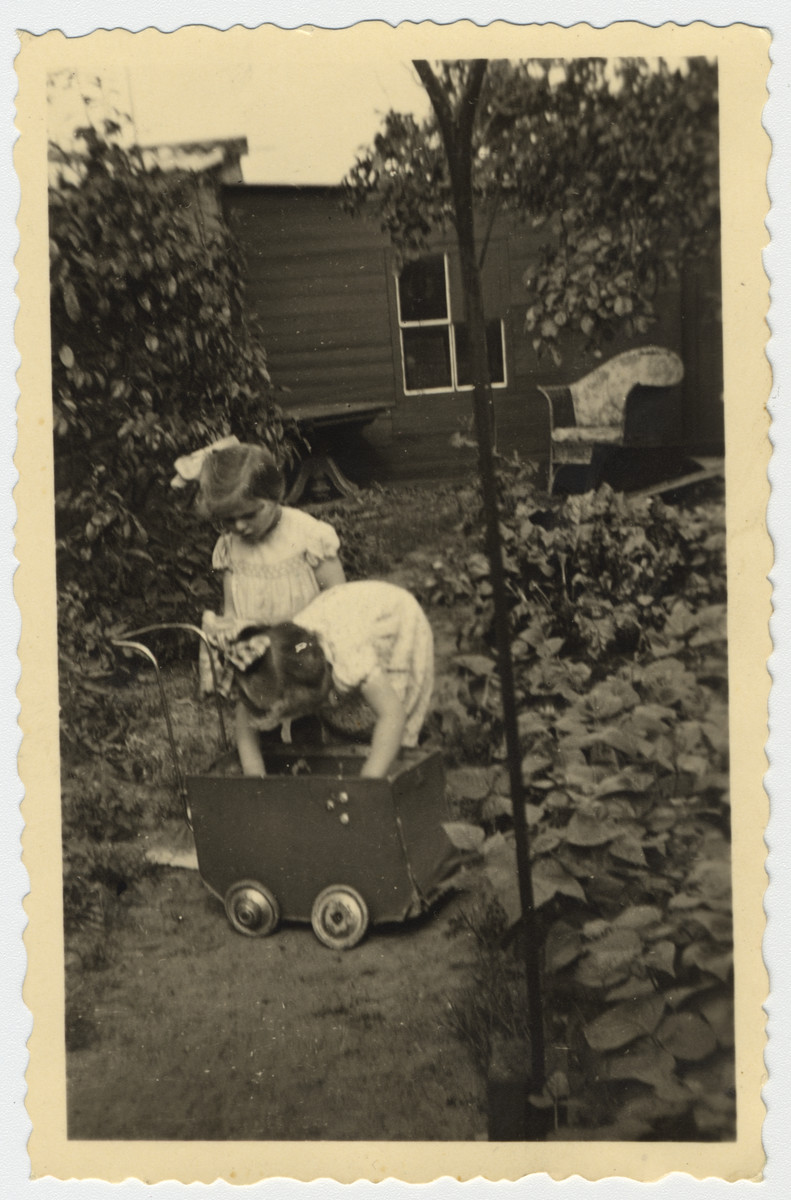 Two Jewish sisters play with a toy baby carriage in a garden while in hiding in the Netherlands.  Pictured are Marjetta and Elisabeth Kleerkoper.