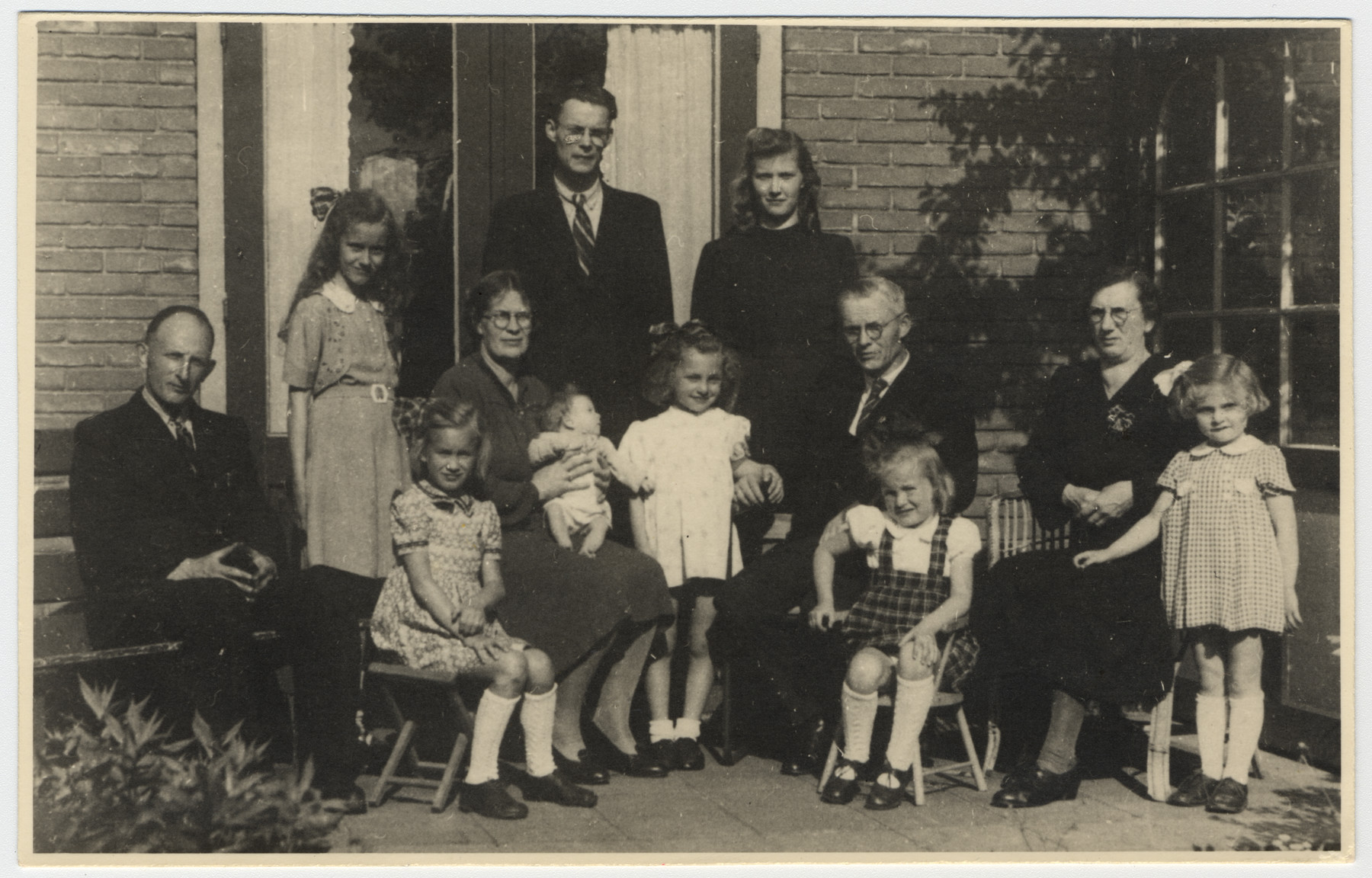 Group photograph of two Dutch rescuers families and the two Jewish sisters they saved.  Pictured on the left are Dirk and Cornelia van der Kamp and their three daughters.  Marjetta Kleerhoper is next to them in a white dress.  Anton and Wilhelmina Heger are seated on the right with Elisabeth Kleerhoper.  The Heger children are in the back.