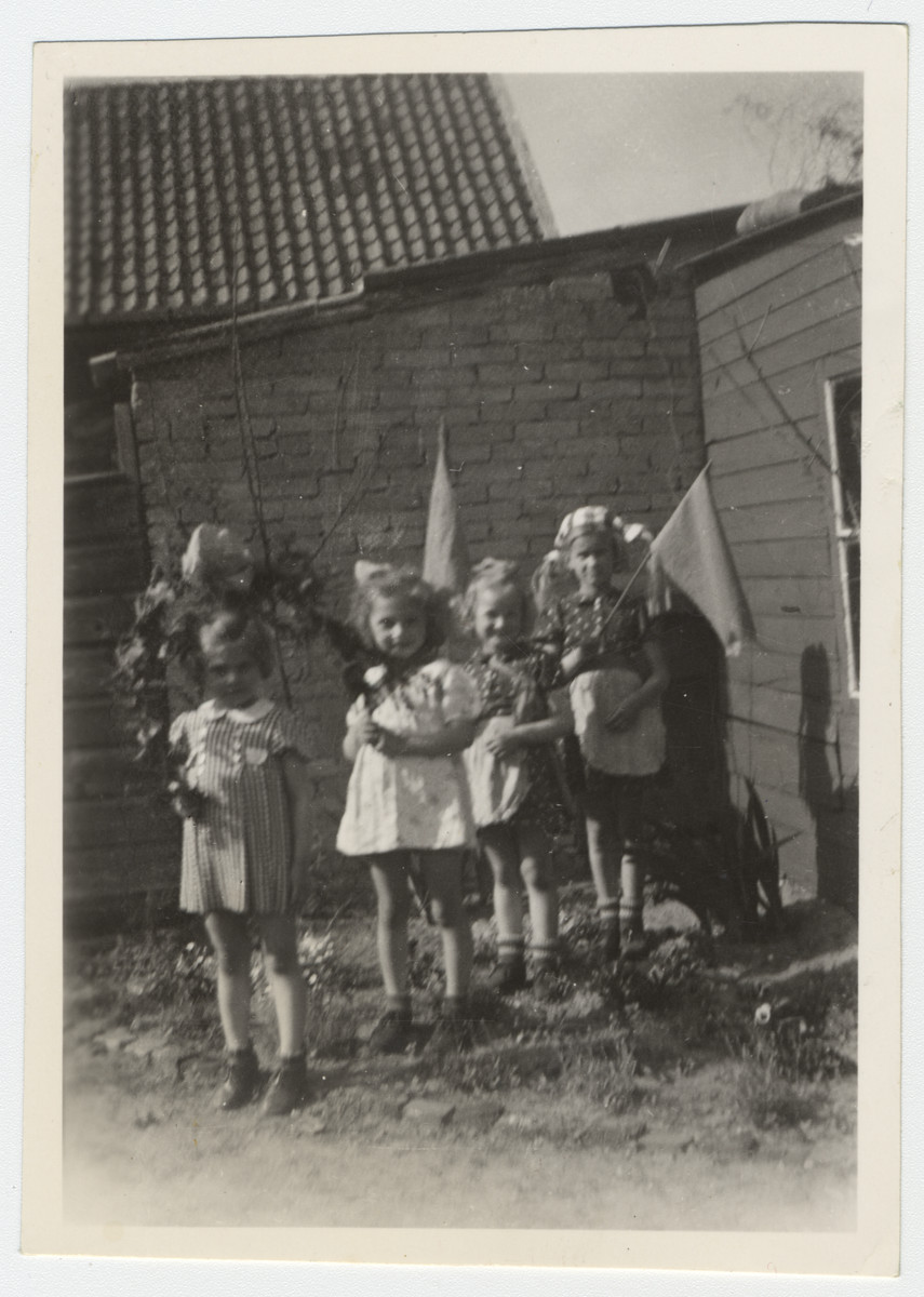 Four young girls, including two sisters in hiding, carry garlands of flowers to celebrate  the end of the war.  Pictured are Marjetta and Elisabeth Kleerkoper.
