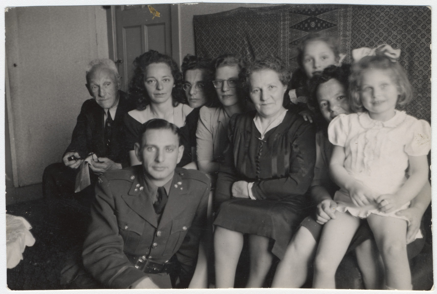 Postwar family of a Dutch Jewish family.  Pictured on the left is Sigmund Kleerkoper in his army uniform and his wife seated behind him.  Their older daughter Marjetta is in the back and Elisabeth is in the front, right.