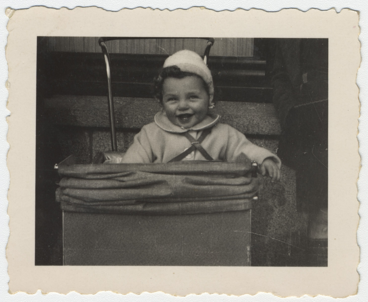 Close-up photograph of a smiling one-year-old in her carriage.  Pictured is Marjetta Kleerkoper.