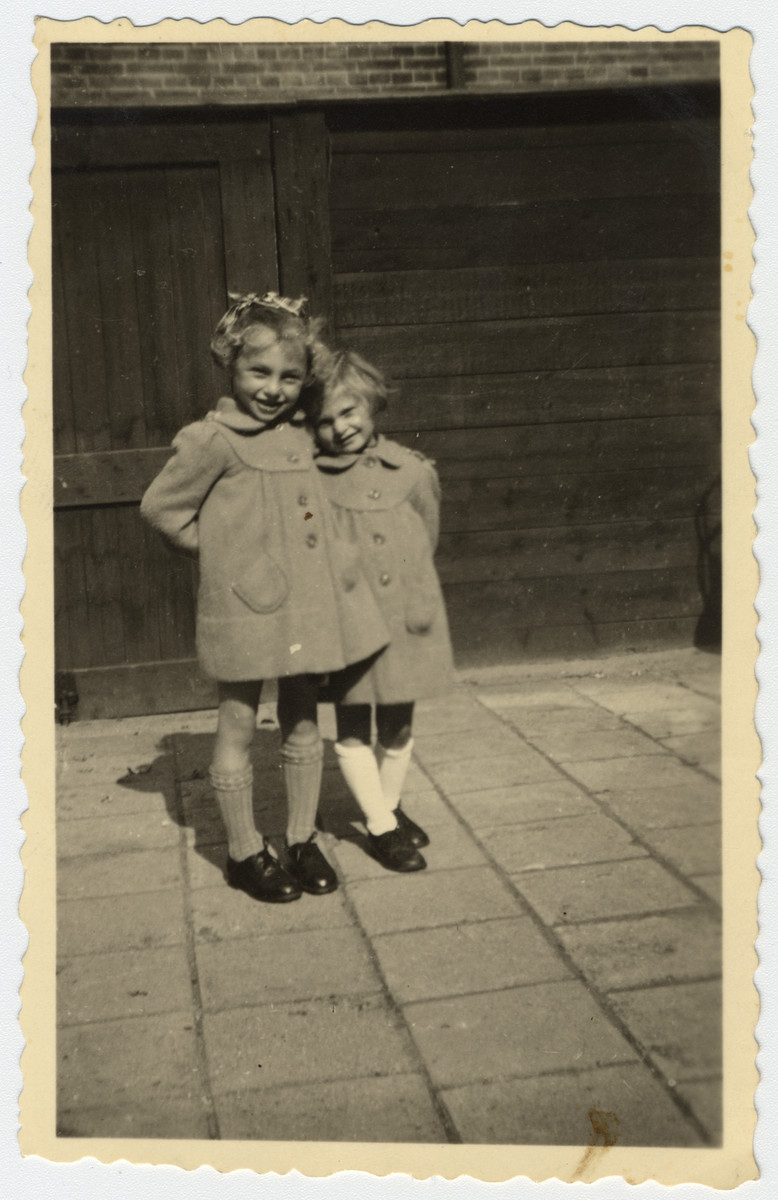 Close-up portrait of two Jewish sisters wearing identical coats taken while in hiding in the Netherlands.  Pictured are Marjetta and Elisabeth Kleerkoper.