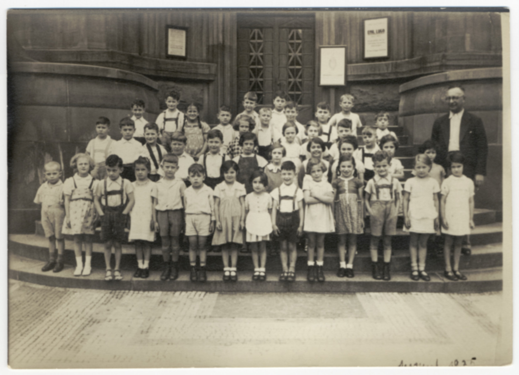An elementary school class poses for a group picture on the steps on a building in Mannheim.  Werner Hirsch is probably pictured in the front row, third from the left.