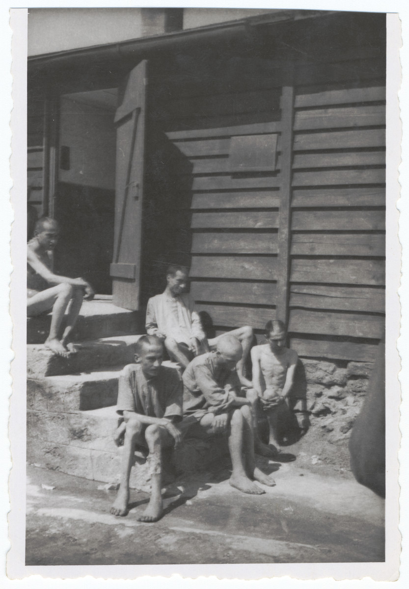 Survivors of the Gusen concentration camp rest on the outside steps of a barracks euphemistically called the Banhoff since the hospital barracks was the railway to heaven.