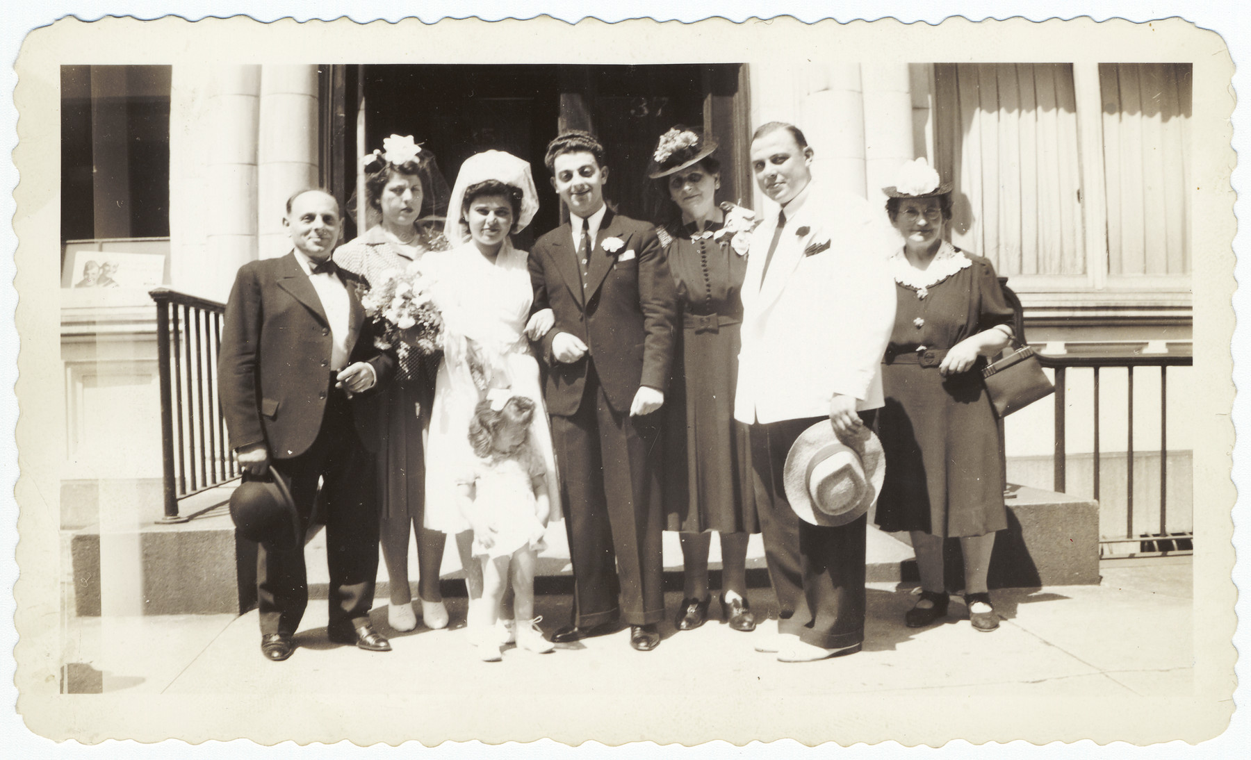 A German-Jewish couple celebrates their wedding surrounded by family members.  Pictured from left to right are Max Hausman (uncle of the groom), Ilse Flehinger (sister of the bride), Martha Sommer, Erwin Hirsch, Milly Hirsch (mother of the groom), Max Sommer (brother of the bride) and Ida Meyer (aunt of the bride).