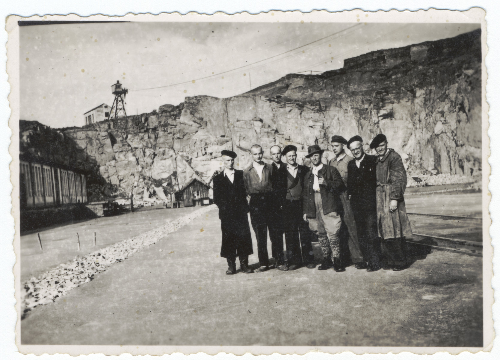 Survivors of the Gusen concentration camp pose in front of the stone quarry.