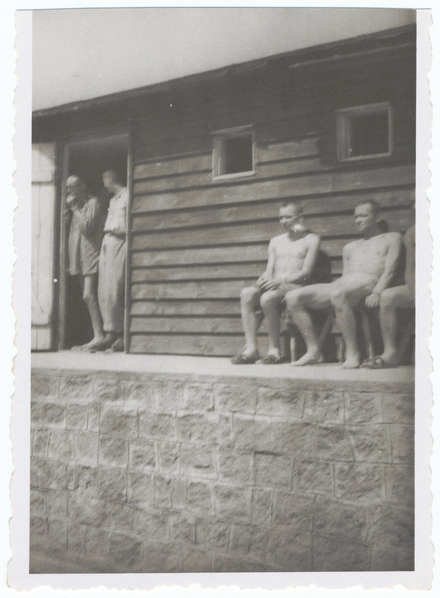 "Survivors of the Gusen concentration camp rest outside the entrance to a barracks that was euphemistically called the ""Banhoff.""     It was given this name because it was used as the hospital barracks where inmates were sent naked, without food until they died (railway to heaven)."