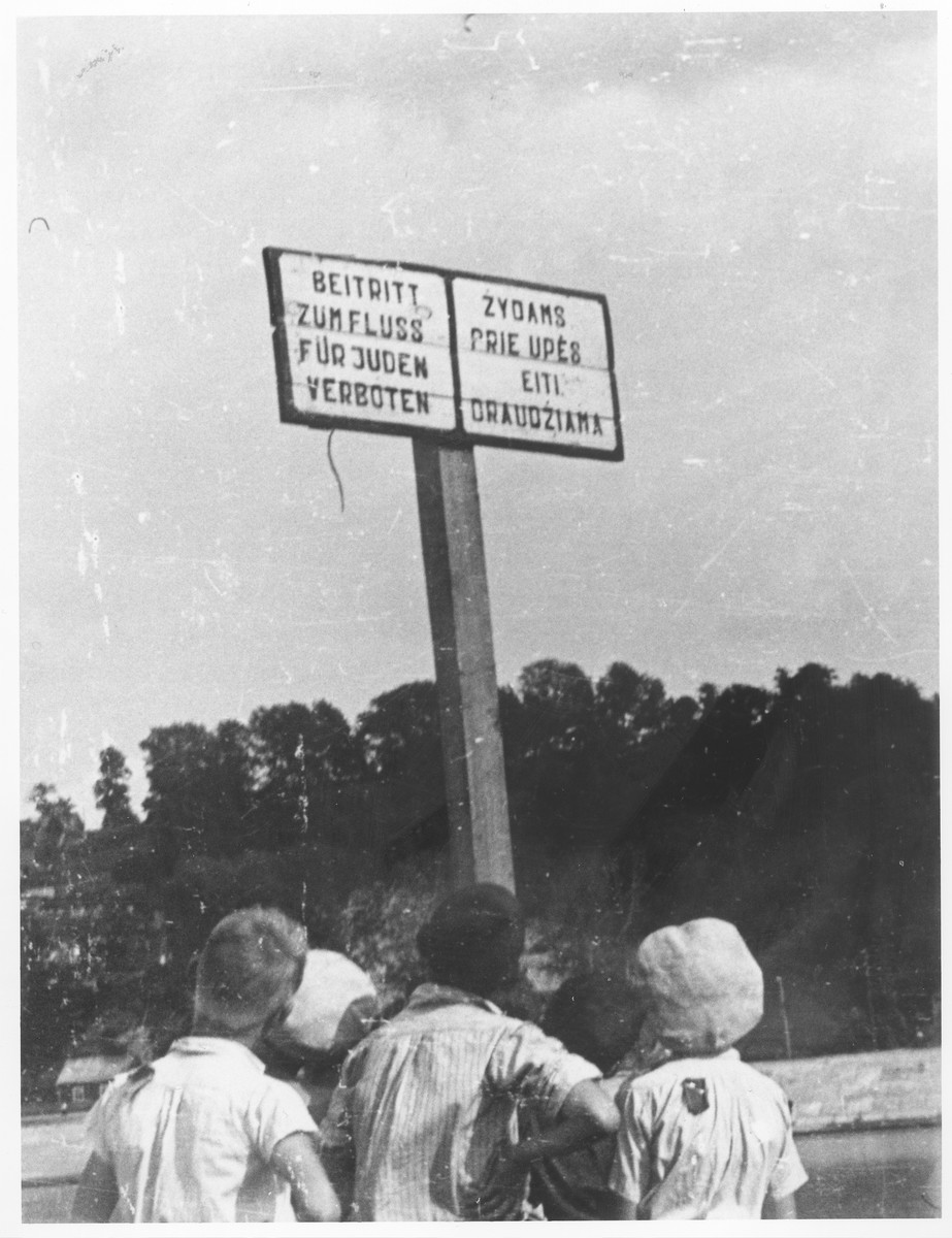 A group of boys look at a sign prohibiting Jews from going into the Vilija River which boarded the ghetto.