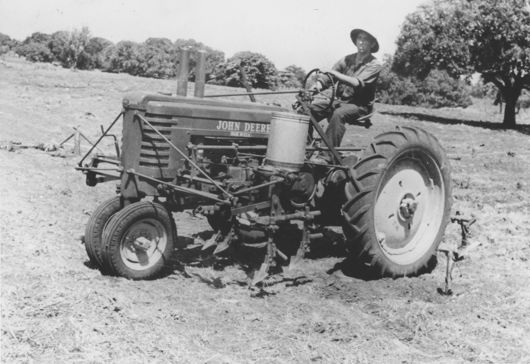 Marek Morsel rides a tractor in the fields of the Sosua refugee colony.