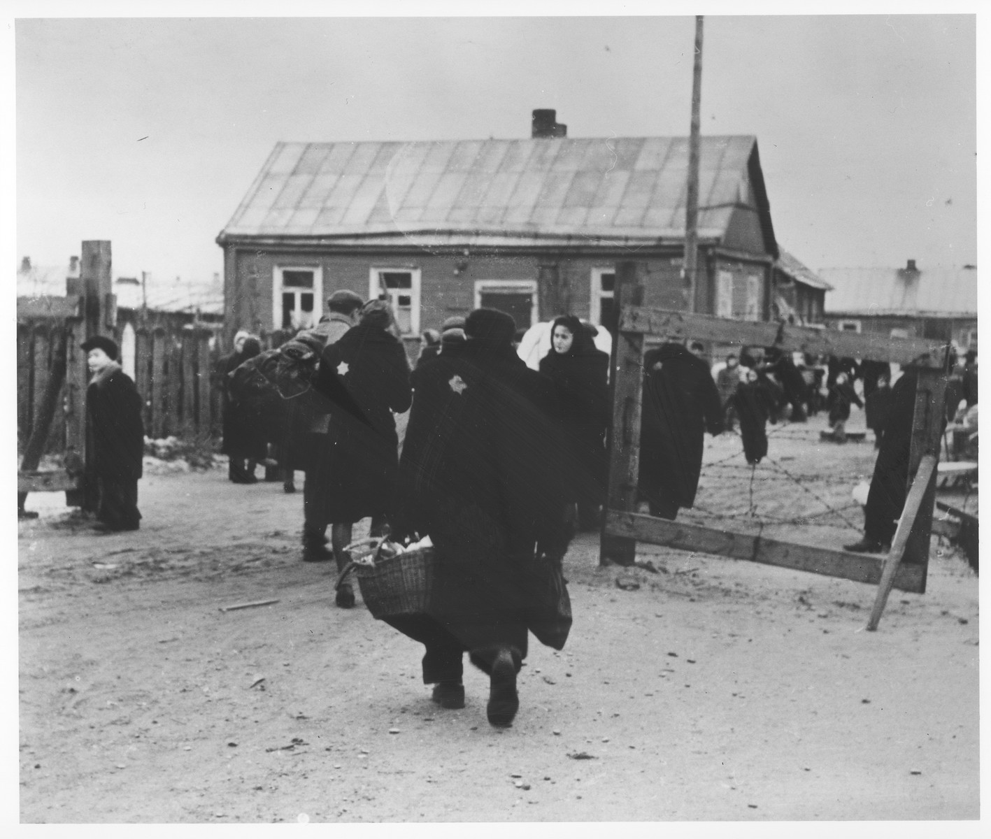 Residents pass in and out of one of the gates to the kovno ghetto.