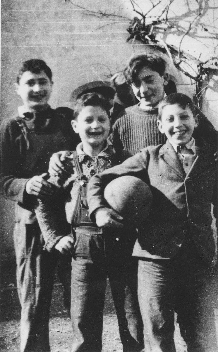 Günter Haas (holding the ball) poses with a group of boys in the Château de la Hille children's home.  Also pictured are Paul Schlesinger (left, center) and Norbert Stueckler (behind Gunter Haas).