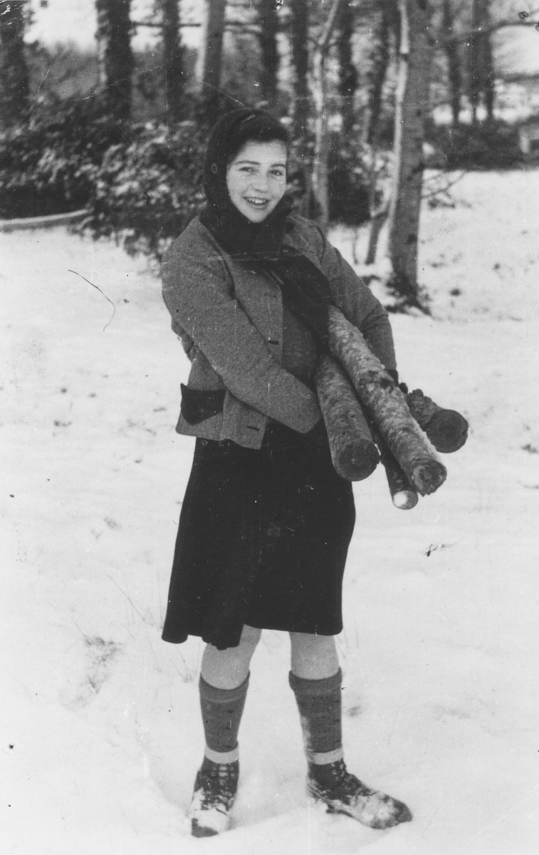 Ingeborg Haas poses in the snow outside the Chabannes children's home carrying a pile of logs.