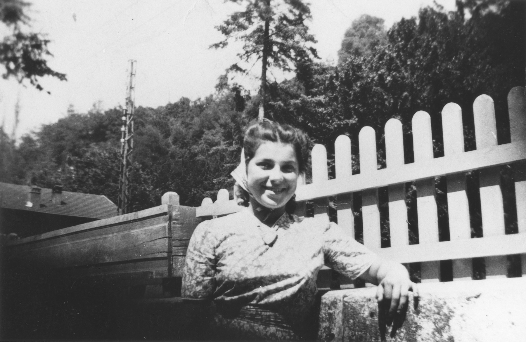Ruth Advokat, a Jewish refugee living at the Chabannes children's home, poses in front of a fence at the farm where she worked near the home.