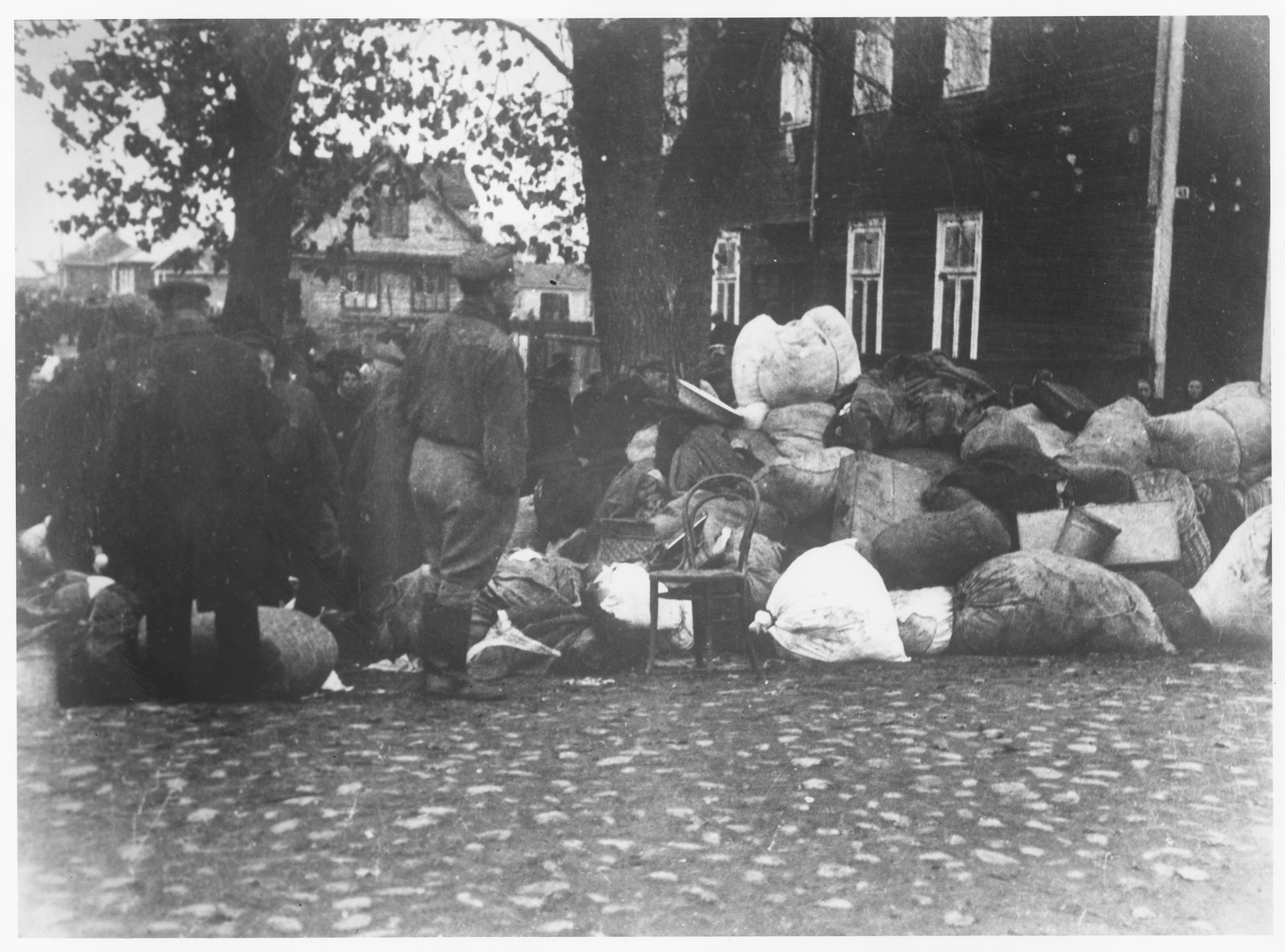 Residents of the Kovno ghetto view a pile of bundles left behind after the last deportation transport .   The possessions that were left behind were taken over by the welfare department of the Jewish Council and distributed to the needy.